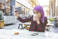 Woman taking selfie on table at sidewalk cafe - CUF16585