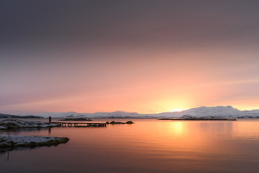 Man standing on pier by lake looking at snow covered mountain at sunset, Thingvellir, Iceland - CUF16600