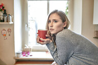 Young woman leaning forward on kitchen counter with cup of coffee - CUF16825
