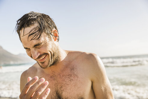 Man with wet hair laughing in sea, Cape Town, South Africa - CUF16978