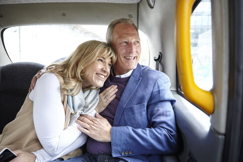 Mature romantic dating couple en route in black cab backseat - CUF17077