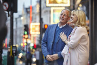 Mature dating couple looking up from city street at dusk, London, UK - CUF17083