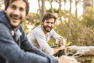 Two men drinking coffee whilst sitting in forest, Deer Park, Cape Town, South Africa - CUF17086