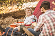 Men camping in forest drinking beer and coffee, Deer Park, Cape Town, South Africa - CUF17101