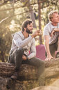 Two male hikers sitting with coffee in forest, Deer Park, Cape Town, South Africa - CUF17107