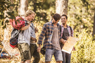 Four male hikers hiking with map in forest, Deer Park, Cape Town, South Africa - CUF17110