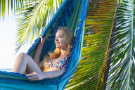 Young woman reclining in hammock at beach, Dominican Republic, The Caribbean - CUF17197