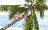 Young woman sunbathing on palm tree at beach, Dominican Republic, The Caribbean - CUF17200