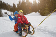 Boy and brother being pulled on toboggan in snow, Elmau, Bavaria, Germany - CUF17260
