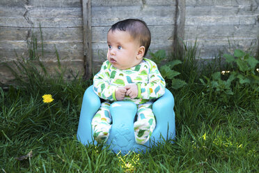 Portrait of cute baby boy sitting in garden on baby support seat - CUF17284