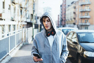 Man in urban area wearing hooded top and headphones looking down at smartphone - CUF17293