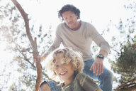 Father and son climbing tree - CUF17302
