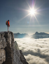 Climber looking out from peak emerging from fog in the Alps, Bettmeralp, Valais, Switzerland - CUF17326