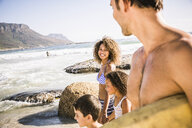 Bodyboarding couple and children strolling on beach, Cape Town, South Africa - CUF17341