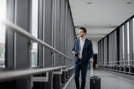 Young businessman in a passageway with cell phone, earbuds and rolling suitcase on the go - DIGF04510