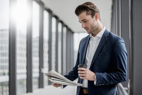 Young businessman standing in a passageway with takeaway coffee and newspaper - DIGF04513