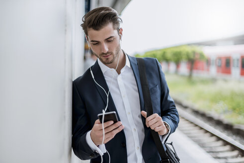 Businessman at the station with earbuds and cell phone - DIGF04522