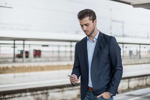 Businessman using cell phone at the platform - DIGF04546