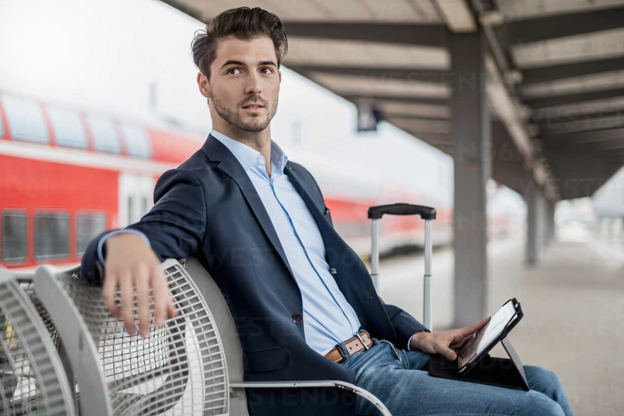 Businessman at the station using tablet - DIGF04549 - Daniel Ingold/Westend61