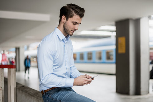 Businessman using cell phone at the station - DIGF04552