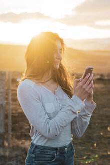 Iceland, woman using smartphone at sunset - KKAF01089