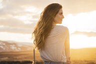 Iceland, young woman at sunset, rear view - KKAF01092