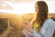Iceland, woman using smartphone at sunset - KKAF01095
