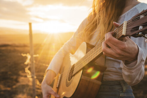 Iceland, woman playing guitar at sunset - KKAF01101