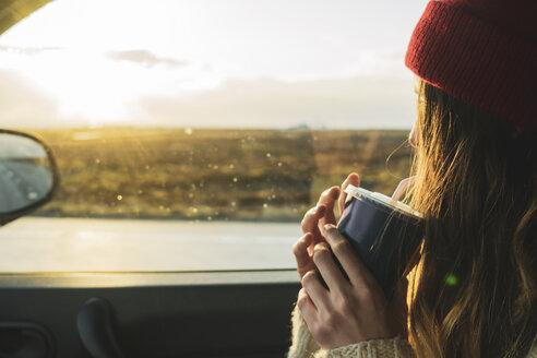 Iceland, young woman with coffee to go in car at sunset - KKAF01113