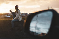 Iceland, young woman with coffee to go at sunset, wing mirror - KKAF01119