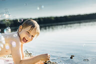 Happy boy at a lake surrounded by soap bubbles - MJF02259