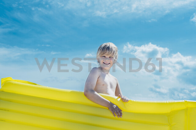 Portrait of happy boy carrying yellow airbed outdoors - MJF02280