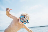 Boy with diving goggles on the beach playing with sand - MJF02292