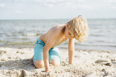 Blond boy playing with sand on the beach - MJF02295