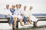 Group of friends, sitting in row on edge of pier - CUF17386