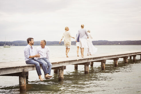 Two male friends sitting on edge of pier, chatting, female friends walking towards end of pier - CUF17389