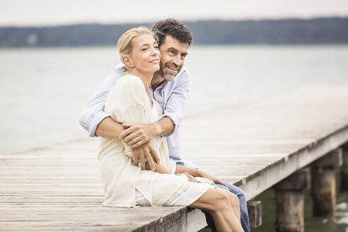 Mature couple sitting on edge of pier, hugging - CUF17392
