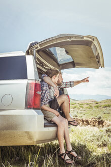 Mature man and teenage son pointing from off road vehicle, Bridger, Montana, USA - CUF17419
