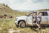 Man and teenage son eating and drinking by off road vehicle, Bridger, Montana, USA - CUF17425