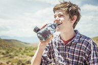 Teenage boy in landscape drinking bottled water, Bridger, Montana, USA - CUF17428