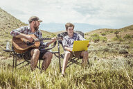 Man and teenage son sitting in camping chairs playing guitar and using laptop, Bridger, Montana, USA - CUF17431