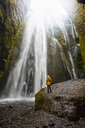 Woman looking up at waterfall, Gljufrabui, Iceland - CUF17437