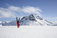 Woman doing handstand on snow-covered field, Litla-heidi, Iceland - CUF17449