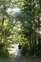 Father and daughter walking through forest, rear view - CUF17473