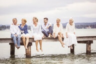 Group of friends, sitting in row on edge of pier - CUF17491