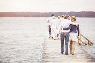 Group of friends standing walking along pier, rear view - CUF17494
