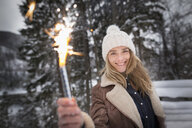 Woman holding smoke flare in winter - CUF17500