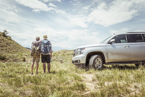 Rear view of man and teenage son on road trip looking out at landscape, Bridger, Montana, USA - CUF17503