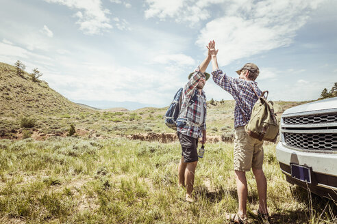 Man and teenage son on hiking road trip high fiving each other in landscape, Bridger, Montana, USA - CUF17506