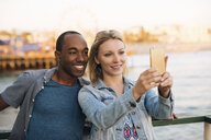 Couple taking smartphone selfie on pier, Santa Monica, California, USA - ISF06633